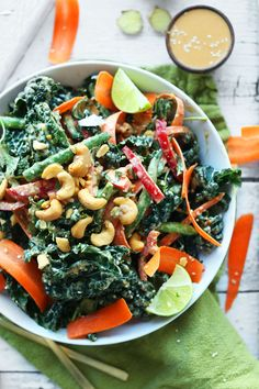 A 30-minute Thai-inspired kale salad with tons of veggies, roasted cashews, and a gingery cashew dressing!