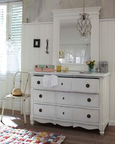 A white distressed wooden drawer chest, a white mirror, a simple crystal chandelier, a vintage style delicate chair, a home made quilt area rug with classic white beadboard wainscoting and distressed paint treatment creates a charming, shabby chic space.