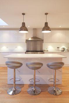 Contemporary sleek white kitchen   Breakfast bar island   Feature pendant lights   Brighton Architects