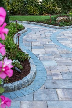 Looking to update your curb appeal? Try adding a landscape wall and some flowers. This walkway by Terra Care Inc features Cambridge Pavingstones with ArmorTec.