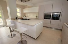 Matt white kitchen and island with tall units in cashmere satin lacquer