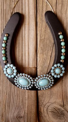 "A decorated horseshoe with a turquoise statement necklace. Silver beads and turquoise blue beads are glued into both grooves of the horseshoe and a wire hanger. This horseshoe measures approximately 4 ½"" x 5"" (just a bit larger than the average size of an adult's palm). I wanted"