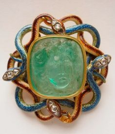 Medusa Cameo. 18 Century. Head of Medusa is a Colombian emerald, mounted in modern enamelled gold clasp representing four interlaced serpents with three diamonds set into each of their heads. Image: British Museum
