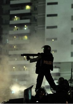 An Indonesian policeman fires tear gas during a clash between police and protesters at a rally against the government's plan to hike fuel prices in Jakarta. Story Inspiration, Writing Inspiration, Character Inspiration, Photographie Portrait Inspiration, Gotham City, Photojournalism, Cyberpunk, A Team, Revolution