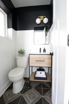 Black + White Powder Room Makeover Powder room makeover with a wood vanity. A powder room makeover with white board and batten and black paint. Love the gold light fixture, wood vanity, and other details in this small bathroom makeover! Powder Room Small, Modern Powder Rooms, Small Bathroom, Wood Vanity, Small Bathroom Makeover, Bathroom Decor, Black Bathroom, Bathroom Makeover, Room Makeover