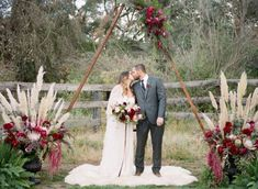 33 Boho Wedding Arches, Altars And Backdrops To Rock: #triangle wedding arch with bold flowers and pampas grass on the sides