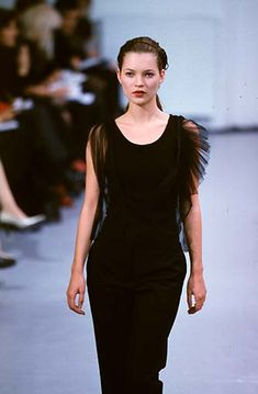 Kate Moss wearing sheer, layered black tank top and pants in the Helmut Lang Fall/Winter 1997 show in Paris.