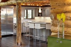 An Adorable Contemporary Log Manor Based On Manor In Colorado : Modern Log Cabin Kitchen Metal Expensive Refrigerator White Kitchen Counter Unique Kitchen Stove Tiny Bar Counter Unique Hardwood Pillar Green Unique Drawer