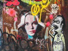 """This woman seems to be slightly confused, surprised, or dazed by the wide look in her eyes and her hands on top of her head. She is very pretty, with fine features she seems to take up this metal wall she was on. Next to her, is the figure with the shirt """"art is trash,"""" making her stand out as one of the clearest, and cleanest figures on the whole facade. She is also looking at the viewer."""