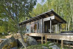 These 8 Log Cabin Kit Homes Celebrate Nordic Minimalism - Photo 7 of 20 - Located on the country's west coast, this wilderness sauna cabin was built with square logs that are four inches thick, and has a 1,028-square-foot outdoor terrace.