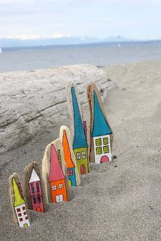 little houses painted on driftwood with paint pen