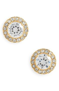Cubic zirconia solitaires rimmed in halos of sparkling pavé make a dazzling pair of stand-by studs.
