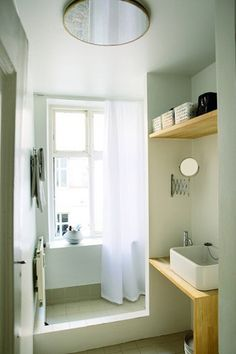 Simple small bathroom. Like the use of the wood and basin sink!