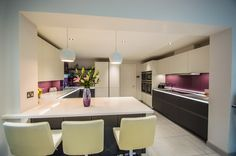 Beautiful handless kitchen from Nolte Kitchens featuring Matrix Art lighting.  This kitchen has grey glass units which contrast beautifully with white matt units and the whole kitchen is enhanced with Raspberry Shimmer glass splash backs.