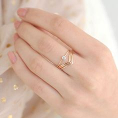 A petite gold diamond ring makes a statement stacked with three chevron rings. At a tiny 3mm, the gemstone is perfectly feminine and