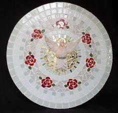 Peça leve e elegante que pode ser colocada em qualquer ambiente, conferindo proteção e aconchego. <br>Mandala em mosaico com pastilhas de vidro e pastilhas cristal e uma imagem do Divino Espírito Santo ao centro, patinada. A peça é feita em tons de branco, rosas vermelhas e o centro, com pastilhas douradas e espelhadas no tom ouro. <br> <br>Tamanho: 40 cm de diâmetro