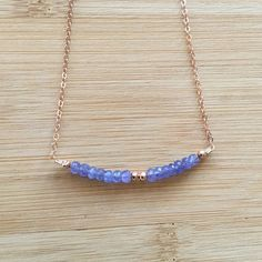 A 14K rose gold filled chain is the perfect match to the violet tanzanites. The gemstones are highlighted with rose gold filled beads. Because these beads are strung, they can curve with the necklace, unlike the ones on a bar. The necklace is 16 in length and fastens with a rose
