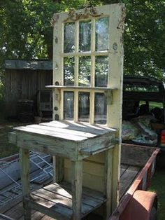 Old door potting bench.  Could put a mirror behind the glass and hooks down each side of door frame and use it in a back room to hang coats on and set stuff on when you come in.
