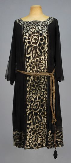 Black chiffon boatneck with long flared sleeve having center front and back panels with metallic gold paint decoration in an abstract floral outlined in tiny beads, attached braided metallic cord belt, silk underdress. B-38, L-43. (Minor bead and paint losses, few tiny holes in chiffon, 1/2 inch tear in back panel) good.  $390