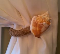 I took my previous curtain tie backs which were rubbed oil bronze with a ornate finials. I unscrewed the finial end and wrapped it with twisted jute twine that I bought at Lowe's fixing it with hot glue as I went.  Then I hot glued a seashell that I found on the beach in California to set it off!  It was really simple and totally changed the look of my dining room curtains/decor.