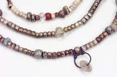 """Necklace with bead pendant from Birka chamber grave. Date. 800-1100.  """"Halsband med 1 pärlhänge (2 pärlor på silvertråd) och 79 pärlor - 3 bergkristall, 1 fajans och övriga av glas."""""""