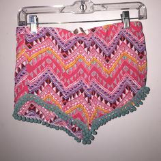Tribal patterned shorts Mostly pink and blue tribal patterned shorts with pom pom trim. Size small but would also got a medium due to stretchy waistband. Shorts