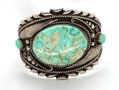 "The turquoise in this bracelet is a soft blue green color with gold matrix and measures just over 1-1/2"" by 1-1/4"". You can see by looking at the side of the bracelet that the stone is very deep. In order or accomidate such a large stone, the silversmith handmade a silver bezel. 