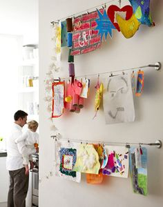 Ideas to Display Kid's Artwork: Rows of curtain wire and clips make it easy to change out kid's art as they create new masterpieces.