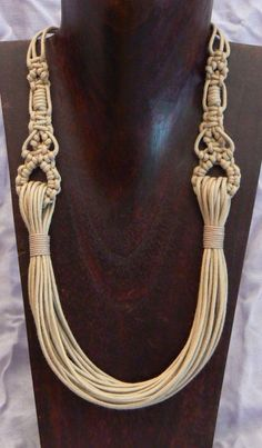 A fun cord (leather?) necklace... smooth strands on the bottom, macrame knots on top.