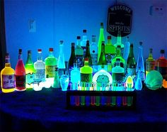 A clever idea from Something Wicked This Way Comes. Set up a small blacklight area - just a bar or a table. Fill bottles with water coloured with food dye and label them with Halloween names like Zombie Parade, Night Tremors or Henbane.