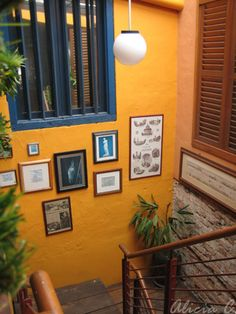 exposed brick, mustard wall, steps, industrial railing...inside décor; looks tropical to me! Cool.