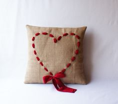 Simply adorable... sew a simple burlap pillow - create a pretty heart using ribbon and a basic running stitch or back stitch (or get adventurous with a whip stitch) - leave excess on each side to tie a bow. Tack bow center in place to ensure it remains tied.