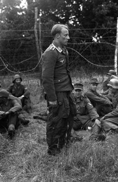 The first Nazi airman to be shot down in the invasion area stands dejected amongst other prisoners at a camp somewhere in England, on June 9, 1944.