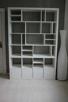 Think outside the box when constructing an Ikea Expedit bookshelf to construct your own custom shelves like this one from Ikea Hackers made from 3 separate Expedit units. o.O