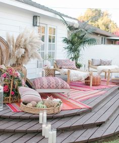 Beautiful raised patio deck with layered pink rugs and floor cushions.