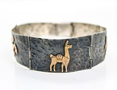 This is a charming vintage hinged panel bracelet crafted circa 1960s/70s. Rendered in fine sterling silver, each panel features a hammered design adorned with an 18k yellow gold Peruvian Incan animal or figure.