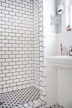 Great white subway bathroom tiles with dark grey grout.