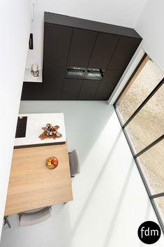 De moderne en strakke greeploos zwarte Fenix keuken is gecombineerd met een geïntegreerde eiken houten tafel en een keramiek marmer look aanrechtblad.