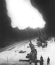 """A battery of German 88mm Flak (for """"Flugzeugabwehrkanone"""", or aircraft defense cannon) guns is seen firing into a formation of RAF night bombers almost five miles above them. It is likely that more Allied bombers were lost to German anti-aircraft fire than to enemy fighters. A central radar unit could control all guns simultaneously, causing barrages of hundreds of shell bursts in one general area and altitude. Though the bombers could not shoot back, Flak was less glorious but quite lethal."""