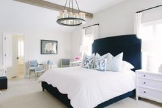 White and navy bedroom features a navy velvet bed with brass nailhead trim dressed with white and ...