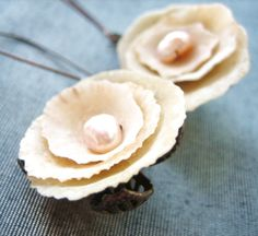 These earrings are made with layers of shells to become beautiful roses. In the centre is a cultivated pearl. The earrings are including the earring wires 2'' (5cm) the roses are 3/4'' (2cm). Made with copper and aged fold filigree, all metal is nickel and lead free.