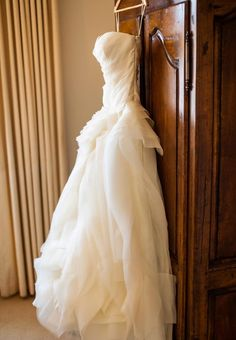 The bride's Vera Wang ball gown rested on its hanger against a natural wood armoire in the bridal suite. Photography: Embrace Life Photography. Read More: http://www.insideweddings.com/weddings/elegant-california-wedding-with-sophisticated-decor/442/