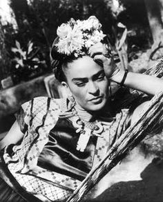 Mexican artist Frida Kahlo wearing traditional Mexican dress at a time when it wasn't fashionable, combined with elaborate and large floral headdresses and Tehuana ribbons in her hair.