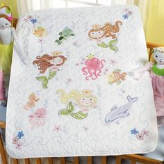 The Mermaid Bay Baby Quilt Kit is a Stamped Cross Stitch crib cover kit from Bucilla.  Kit includes a pre-quilted, pre-finished poly/cotton quilt, cotton floss, floss separator, needle, chart and instructions.  The cross stitch design is pre-printed on the quilt in wash-away ink.  Baby quilt measures 34 in x 43 in.  The Mermaid Bay crib cover is a fun under the sea themed stamped cross stitch pattern for baby. $43.95