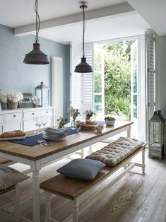 This kitchen has all the elements of New England style - scrubbed wooden floors, painted furniture, metal lighting and white shutters at the French doors. Inspiration from www.thecaliforniacompany.co.uk #shutters