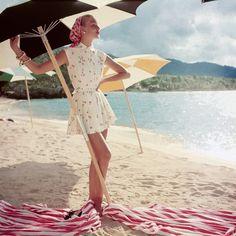 Model standing under beach umbrella, 1954
