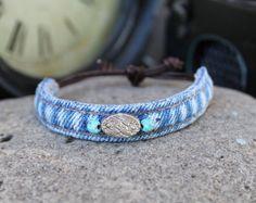 Il s'agit d'un bracelet à la main, conçu à partir des coutures des jeans en denim recyclé. La fermeture est construite à partir de cuir avec chaque extrémités fixée avec un noeud et accentués avec des perles bleus ajoutés aux extrémités pour une touche supplémentaire de la sangle.  Dimensions: Les plages d'ouverture d'environ 10 à 7 avec les sangles de fermeture tiré au maximum.  Cet article peut être commandé personnalisé afin que nous puissions créer un bracelet impressionnant à votre…