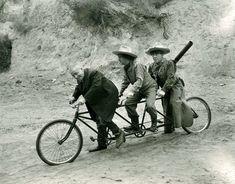 Curly Howard, Larry Fine and Moe Howard ride a bike.
