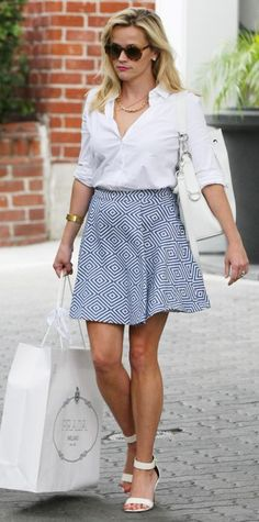 Reese Witherspoon wearing a crisp white button-down tucked into a printed flared skirt, with a white Ralph Lauren drawstring purse and white sandals.
