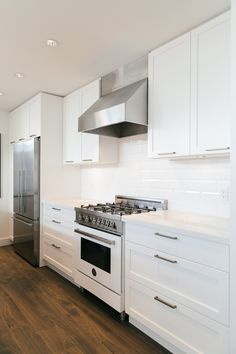 JAMES WALK kitchen:  • Bertazzoni range • Dropped ceilings • Peninsula kitchen with plenty of cabinet and countertop space • Custom, full-height, open shelving • White, shaker-style cabinets with contemporary bronze or vintage brass pulls
